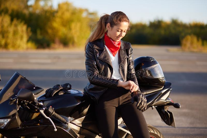 People, protection and driving concept. Pretty woman biker puts on protective gloves, helmet, prepares for driving on motorbike, p stock images
