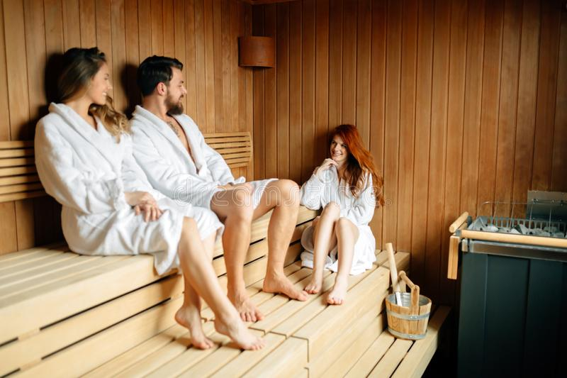 People pursuing healthy lifestyles relaxing in sauna and smiling royalty free stock photo