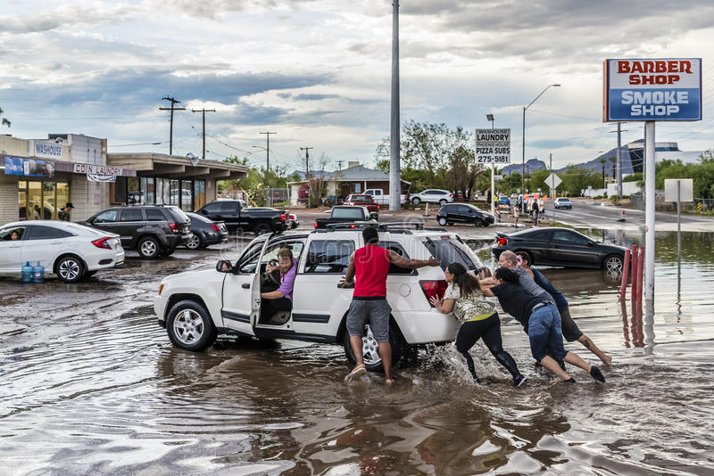 People Push Stalled Vehicle. Phoenix, Arizona, USA - August 3, 2017: Good Samaritans push a stalled vehicle out of a flooded street. Heavy rains inundated much royalty free stock photography