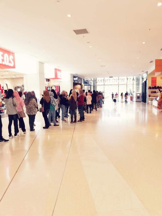 People queuing at a mall stock images