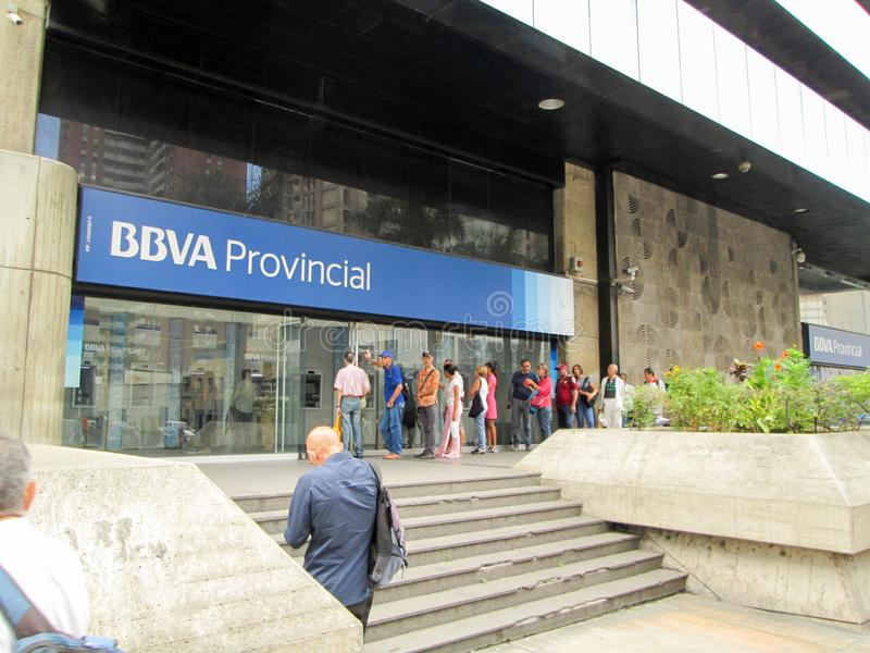 People queuing to withdraw money from ATMs of the BBVA Provincial Bank, at its headquarters.  stock photo