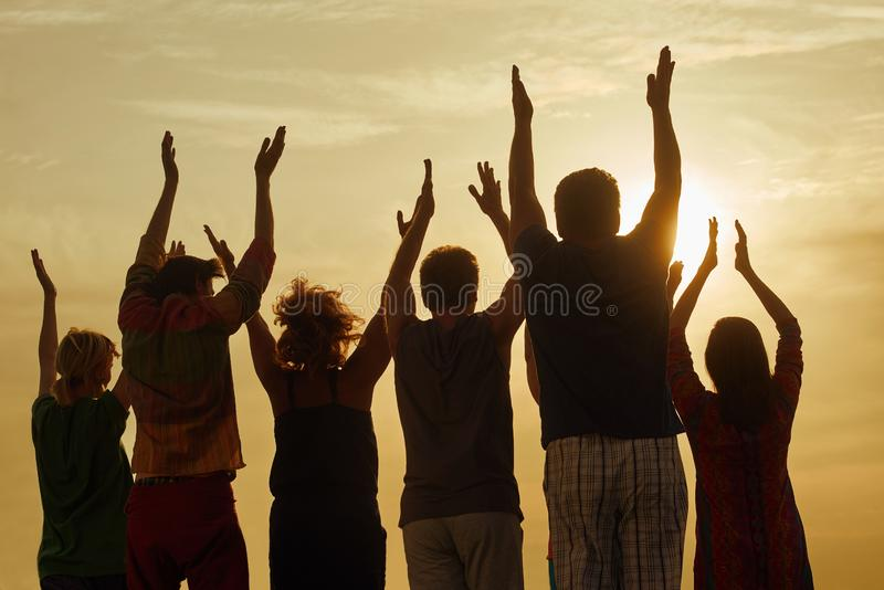 People raising hands up at the sky. Silhouette of family standing with hands up at the sunset stock image