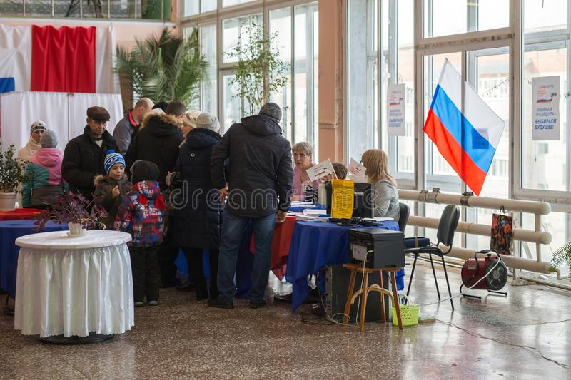 People receive voting ballots at a polling station of the presidential election - 2018. royalty free stock photos