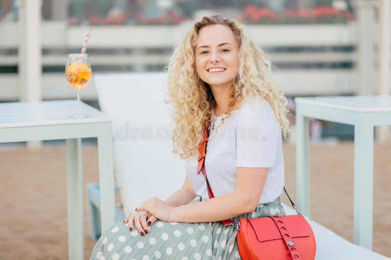 People and recreation concept. Lovely young female with curly bushy hair, wears t shirt and skirt, has bright small bag, rests out stock photo