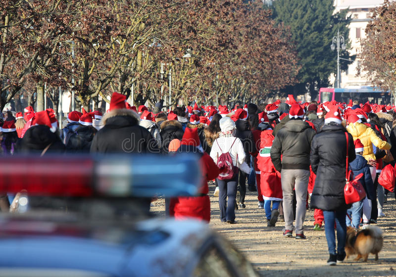 People with red Santa Claus hat and the sirens of police car. Many people with red Santa Claus hat and the sirens of police car escort royalty free stock photography