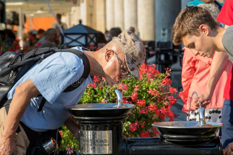 People refreshing at fountain in sweltering hot days on Main Square in Cracow. Cracow, Poland - July 5, 2018: People refreshing at fountain in sweltering hot royalty free stock photography