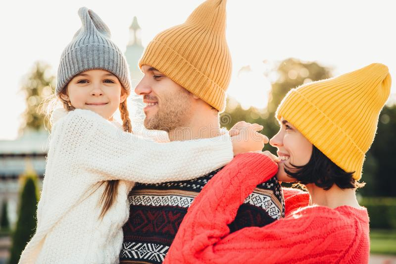 People and relationship concept. Family have unforgettable time together, embrae each other, wear trendy knitted hats. Adorable sm royalty free stock photos