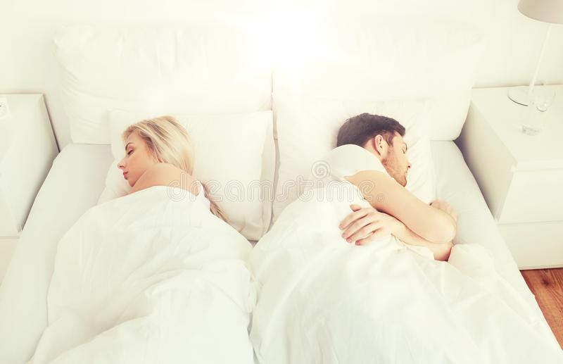 Couple sleeping in bed at home. People, relationship difficulties, conflict and family concept - couple sleeping back to back in bed at home stock photography