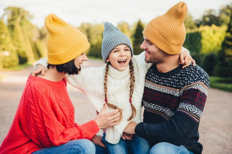 People, relationship and family concept. Smiling little girl with pigtails embrace her parents, express her positive emotions and stock image