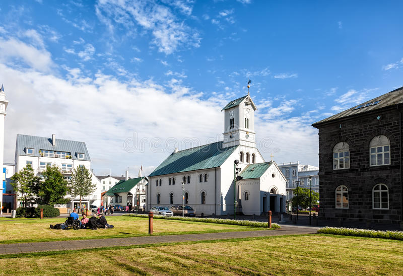 People relax on the grass next to the church in the center of Re. REYKJAVIK, ICELAND -JUNE 27, 2014: People relax on the grass next to the church in the center royalty free stock photo