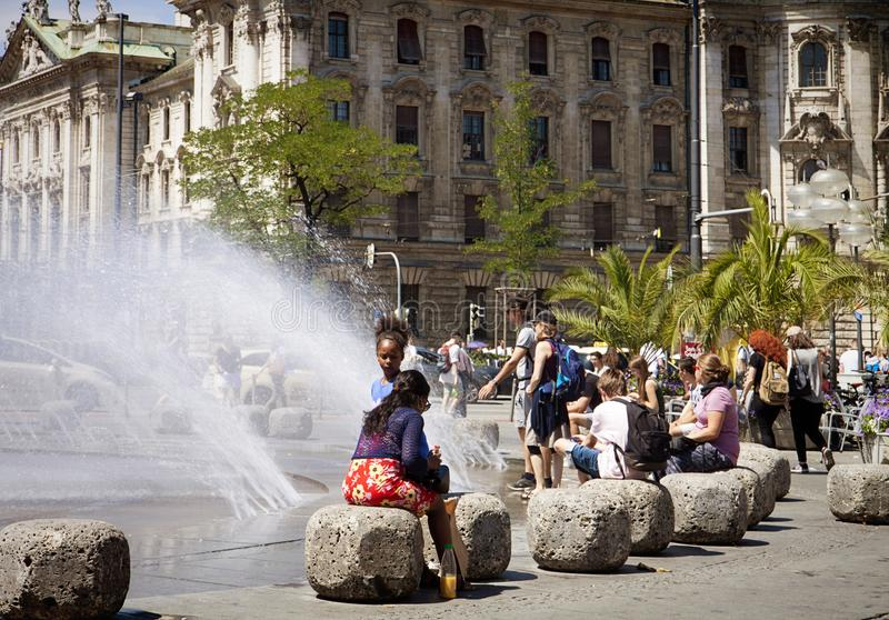 People relax near the fountain at Karlsplatz, Munich stock images