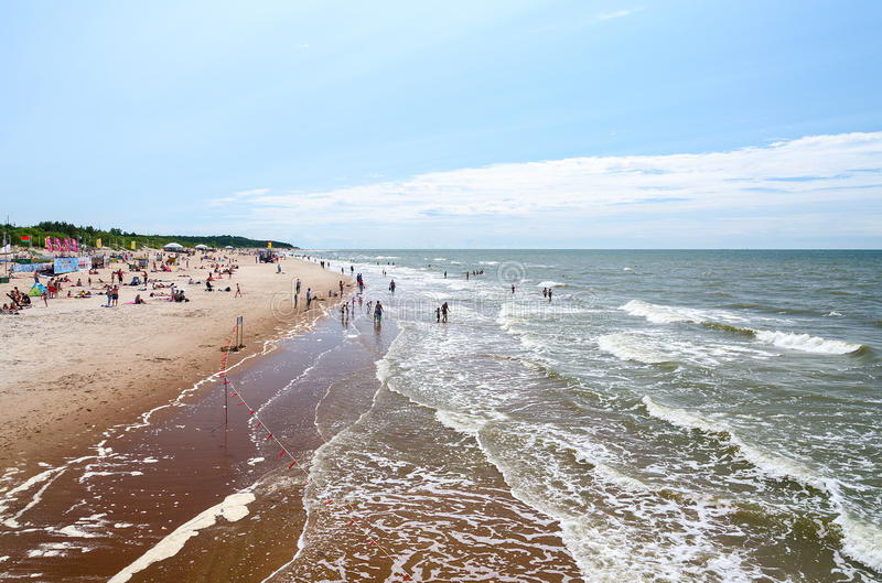People are relaxing on beach in Palanga, Lithuania. PALANGA, LITHUANIA - JULY 12, 2015: Unidentified people are relaxing on the beach in Palanga, Lithuania stock photography