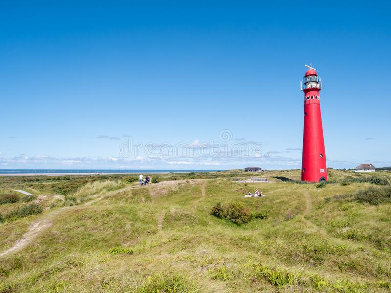 People relaxing near lighthouse in dunes on Frisian island Schiermonnikoog, Netherlands royalty free stock photography