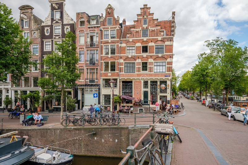 People relaxing on the Prinsengracht, Amsterdam. People enjoying a beautiful day in front of an historical canal house on the Prinsengracht, Amsterdam stock images
