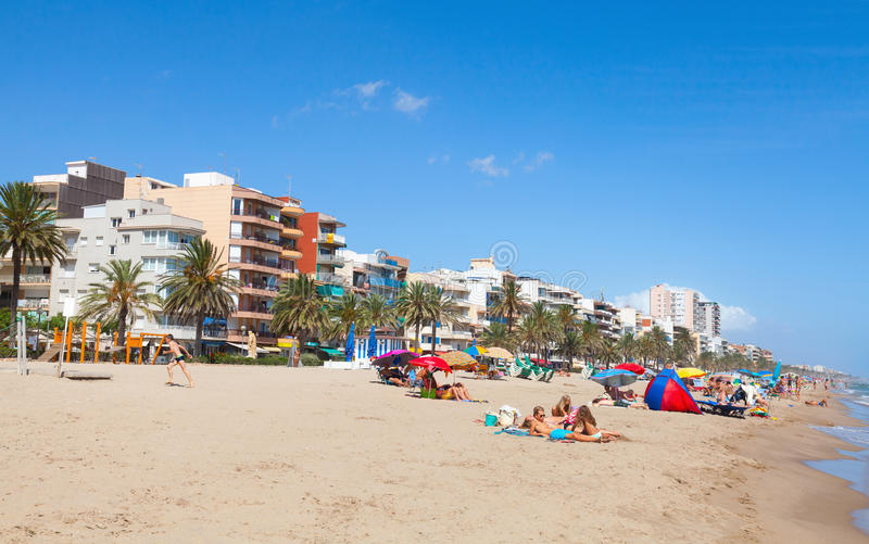 People relaxing on sandy beach of Calafell, Spain. Calafell, Spain - August 13, 2014: People relaxing on sandy beach of Calafell resort town in sunny summer day stock image