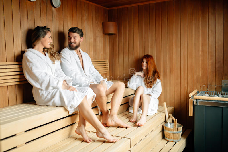 People relaxing in sauna stock images