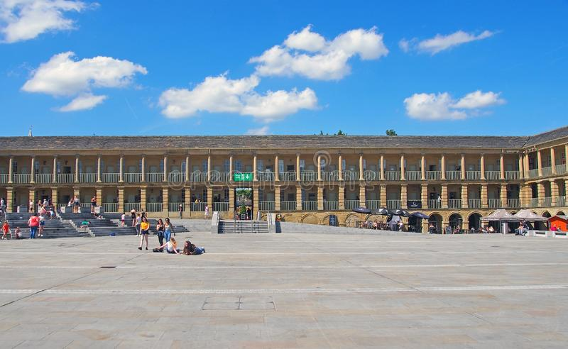 People relaxing on the steps and walking across the square of halifax piece hall in west yorkshire. Halifax, west yorkshire, united kingdom - 23 july 2019 stock image