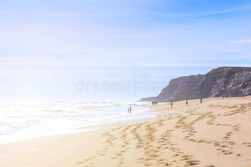 People relaxing and walking on the ocean beach in a shine bright light  at sunny day. Wonderful romantic seascape of ocean royalty free stock photo