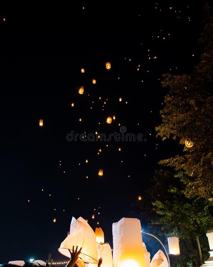 People releasing paper lanterns during Loi Krathong and Yi Peng festival stock image
