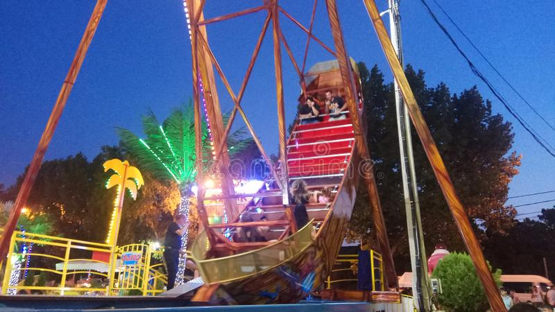People rest in amusement park ride on a swing stilized as old sail boat. ANAPA, RUSSIA - AUGUST 2, 2018: Unidentified people rest in amusement park ride on a royalty free stock photography