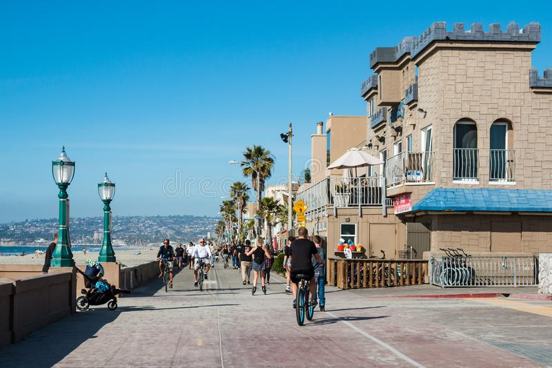 People Ride Bikes on Mission Beach Boardwalk in San Diego royalty free stock photography