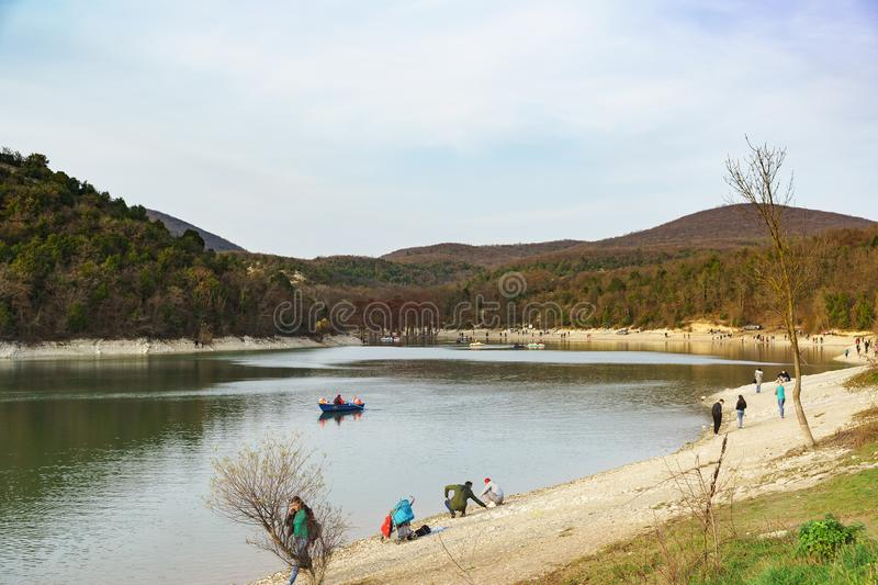 People ride boats and walk around the lake in warm autumn day stock image