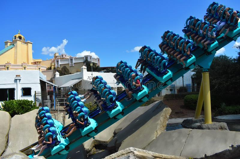 People ride Kraken Roller Coaster at Seaworld Theme Park. Several are screaming. royalty free stock photo