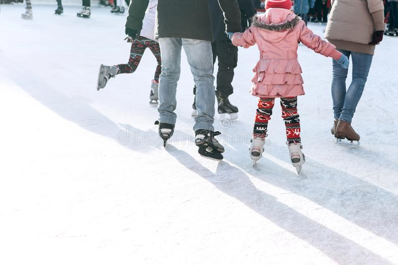 People ride on the skating rink on the ice rink during the Christmas holidays. Sports and fun pastime royalty free stock photography