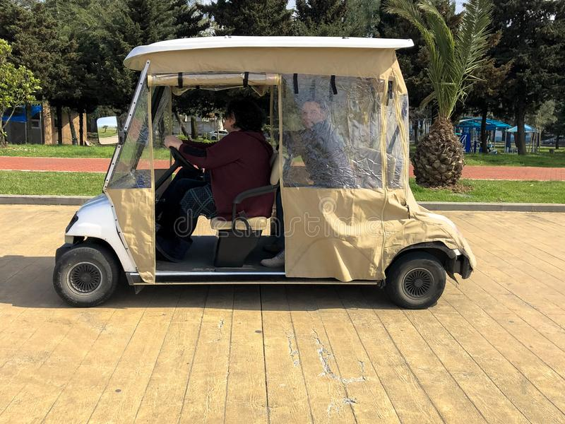 People ride in a small electric car, a golf car on the seafront on a sandy beach. Georgia, Batumi, April 17, 2019. People ride in a small electric car, a golf royalty free stock images