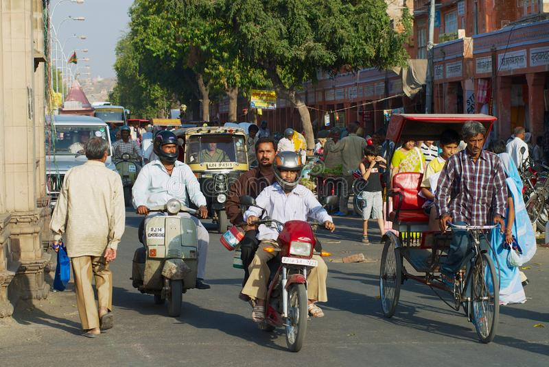 People ride by the street during morning rush hour in Jaipur, India. Jaipur, India - March 30, 2007: Unidentified people ride by the street during morning rush royalty free stock images