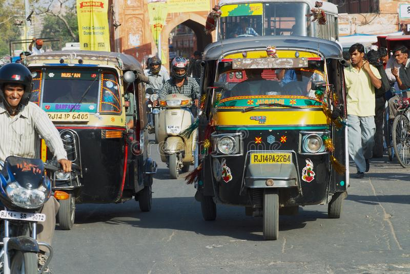 People ride tuk-tuks and motorbikes by the street during morning rush hour in Jaipur, India. Jaipur, India - March 30, 2007: Unidentified people ride tuk-tuks stock photo