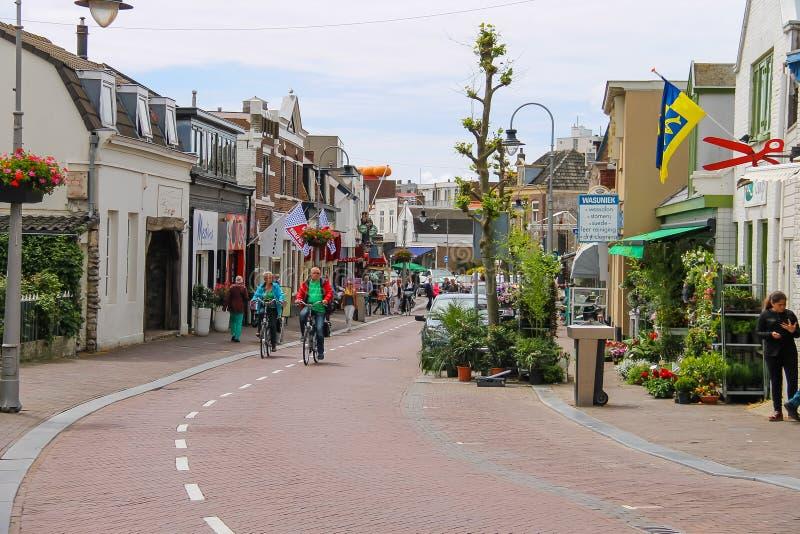 People riding bicycles on Haltestraat street in Zandvoort royalty free stock image