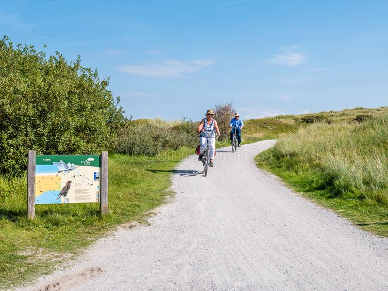 People riding bikes and information board in dunes of nature reserve Het Oerd on West Frisian island Ameland, Friesland, royalty free stock photo