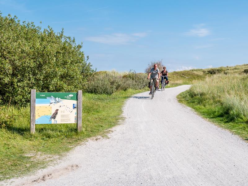 People riding bikes and information board in dunes of nature reserve Het Oerd on West Frisian island Ameland, Friesland, stock photo