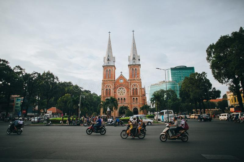 People riding motorbikes on road near church and modern buildings in Ho Chi Minh, Vietnam. HO CHI MINH, VIETNAM - 03 JANUARY, 2018: people riding motorbikes on stock photos