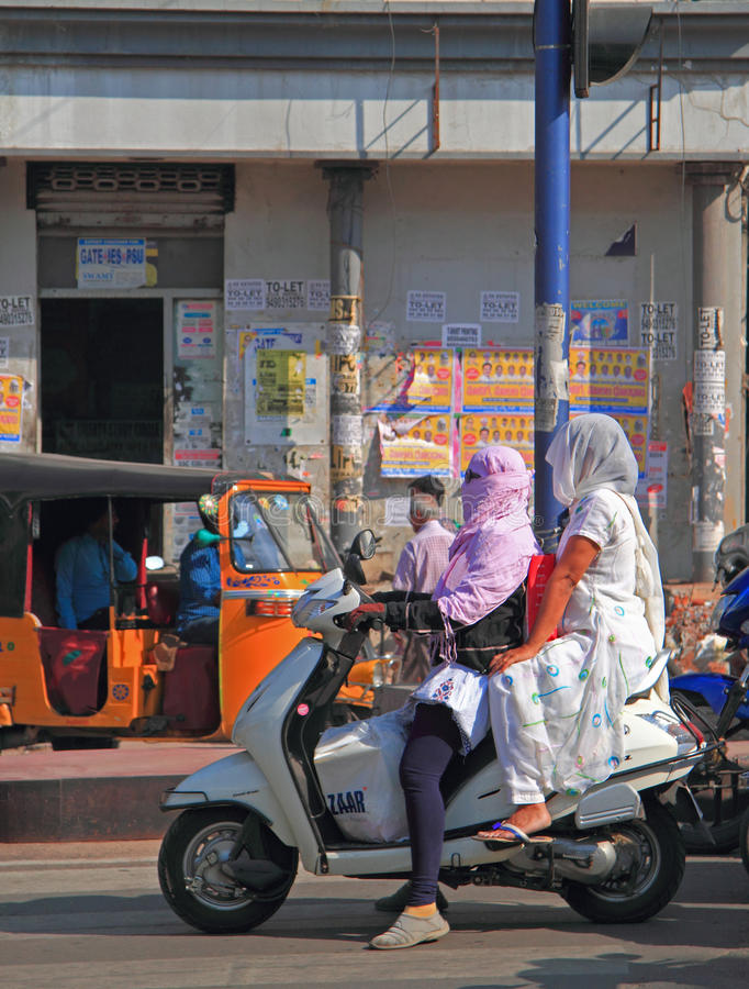 People are riding on motorcycle in Hyderabad, India. Hyderabad, India - March 11, 2015: people are riding on motorcycle in Hyderabad, India royalty free stock images