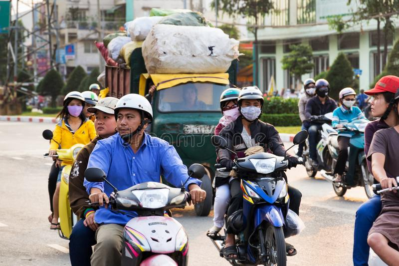 People riding scooters on a busy street in Ho Chi Minh City, Vietnam stock images