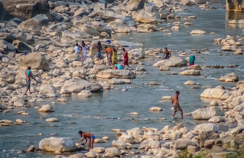 People in the river. Poor nepali families doing daily chores in the river - washing clothes, dishes and themselves, Butwal, Nepal royalty free stock image