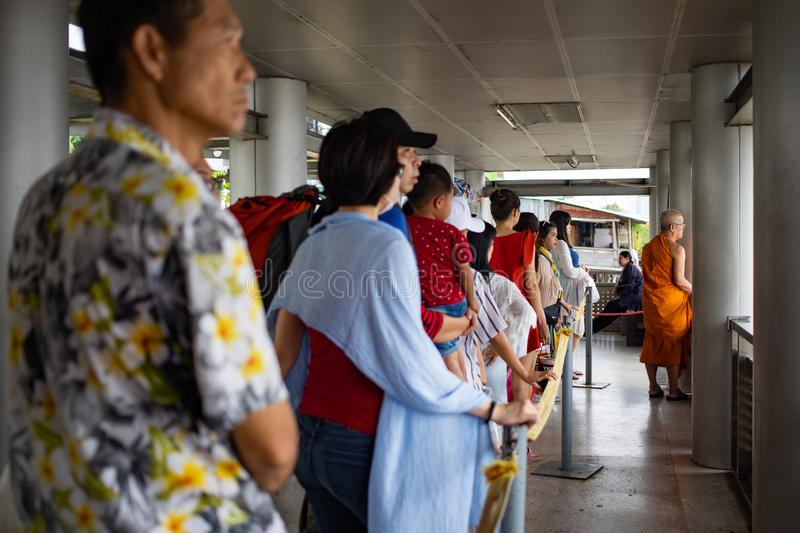 People in row waiting for boat on the pier stock photo
