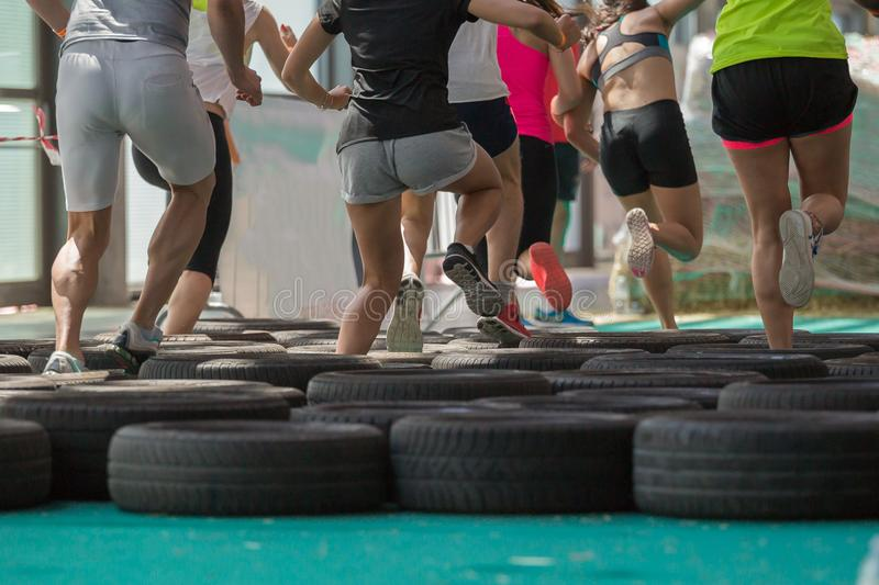 People Running over the Tyre During Fitness Obstacle Exercise.  royalty free stock photo
