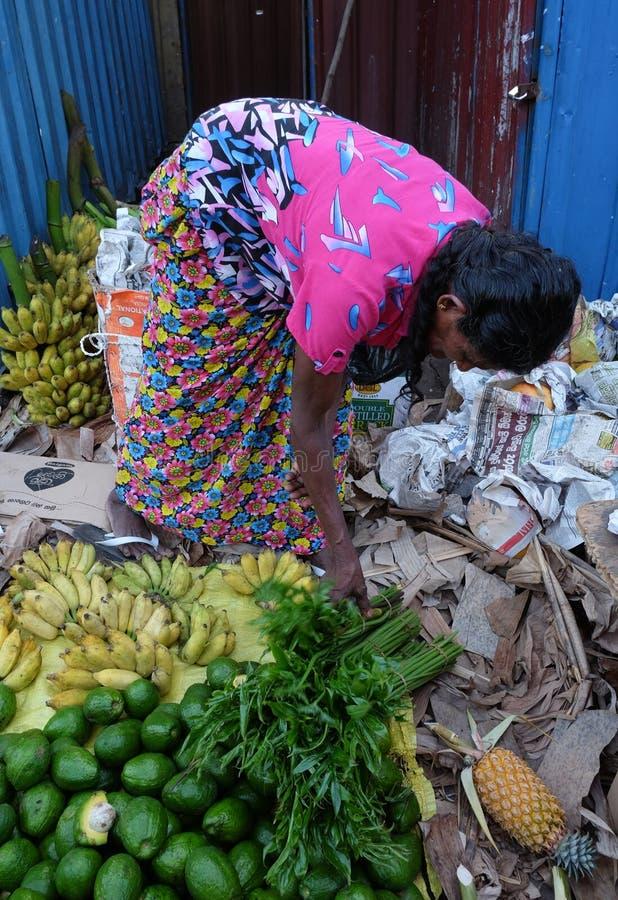People at a rural market in Colombo, Sri Lanka. Colombo, Sri Lanka - Sep 5, 2015. A woman selling fruits at local market in Colombo, Sri Lanka. Colombo is the royalty free stock image