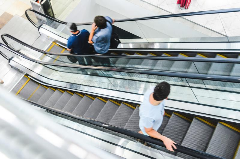 People rush on escalator motion blurred stock photography