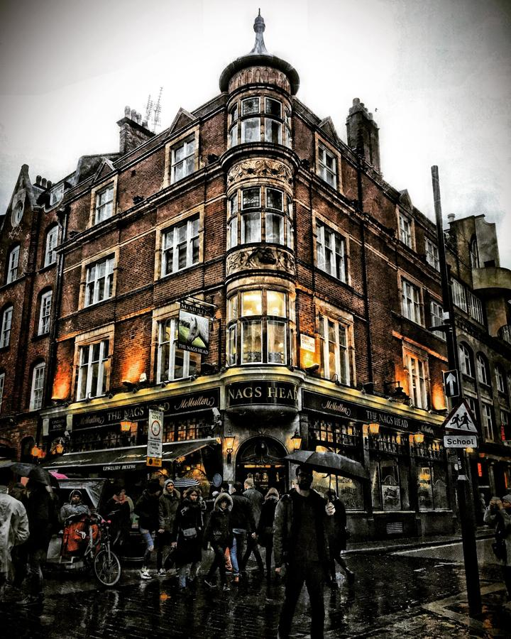 People rush by London Pub exterior in evening light at Covent Garden stock photos