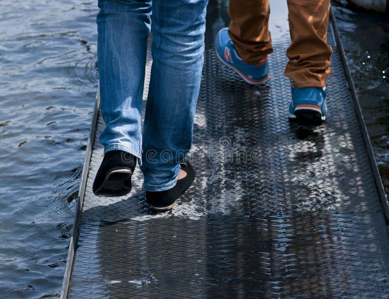 People's legs on the metal bridge. People's legs on the metal bridge under water royalty free stock images