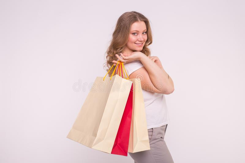 People, sale and consumerism concept - Beautiful woman over white background holding shopping bags royalty free stock photo