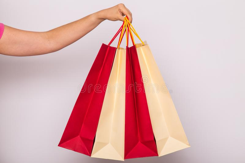 People, sale and consumerism concept - close up of female hand with shopping bags over white background royalty free stock image