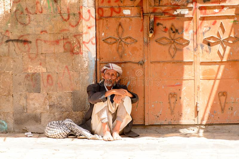 People in Sana'a, Yemen. SANA'A, YEMEN - JAN 11, 2014: Unidentified Yemeni old man sits in the street. People of Yemen suffer of poverty due to the unstable royalty free stock photo