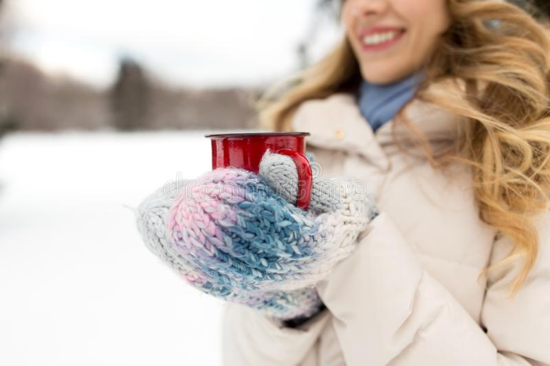 Happy young woman with tea cup in winter park stock photography
