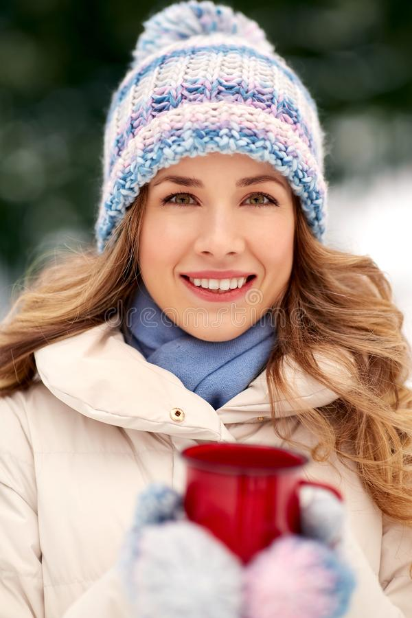 Happy young woman with tea cup outdoors in winter royalty free stock images
