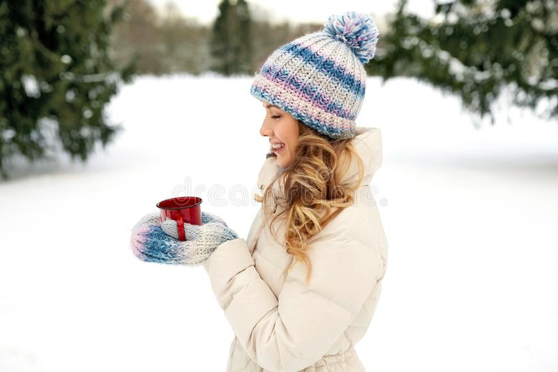 Happy young woman with tea cup outdoors in winter stock photography